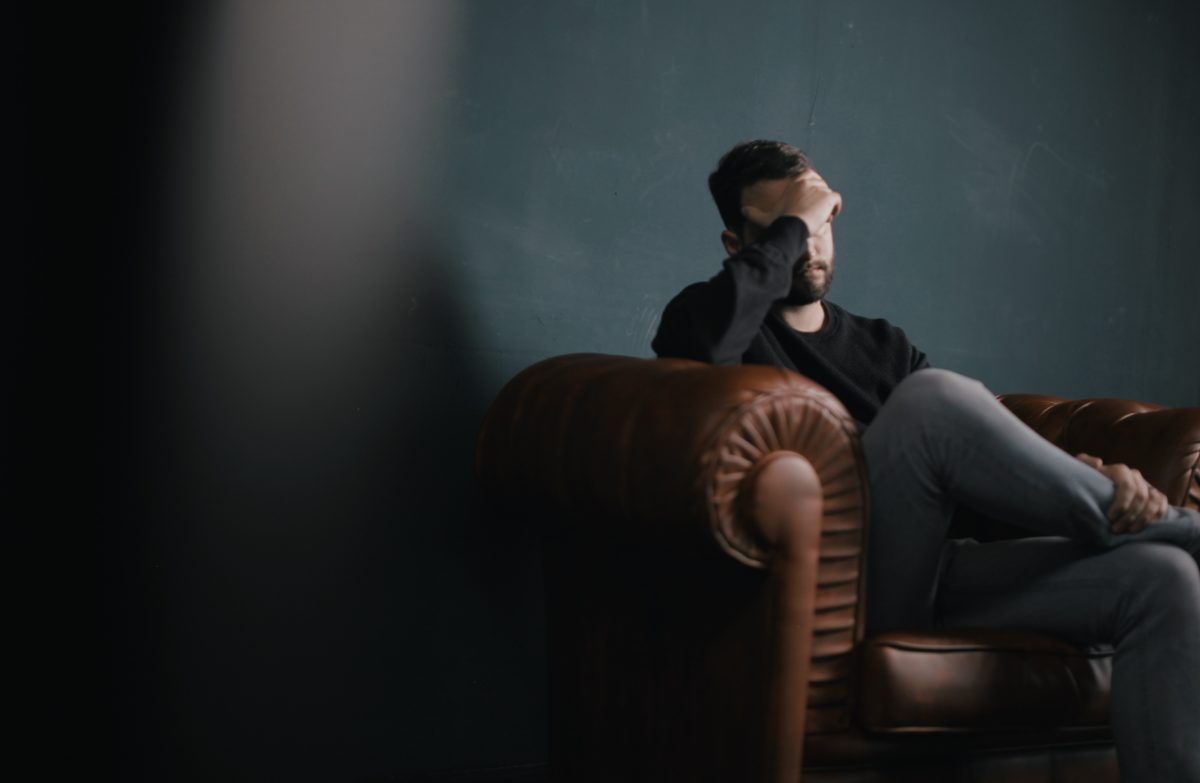 man in chair looking stressed